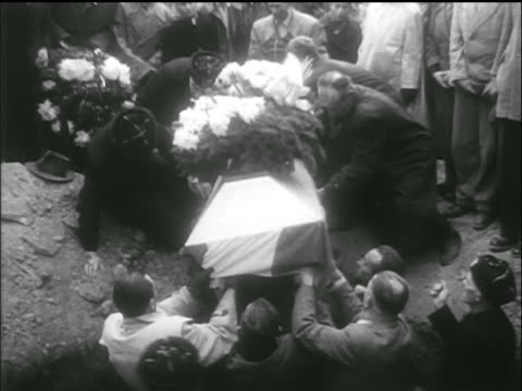 people lower flag + lower covered coffin into large hole / hungarian uprising - 1956 stock-videos und b-roll-filmmaterial