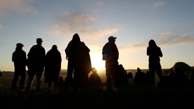 vídeos y material grabado en eventos de stock de people make their way up the bank to watch the sun rise at the avebury stone circle in wiltshire, where they gathered to celebrate the dawn of the... - solsticio de verano