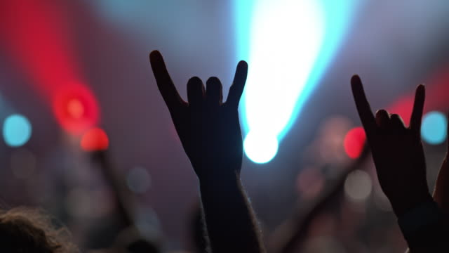 people making rock and roll hand gesture at night concert - rock and roll video stock e b–roll
