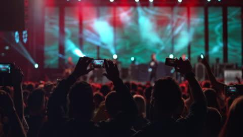 ds people making smartphone videos of a night concert - konzert stock-videos und b-roll-filmmaterial