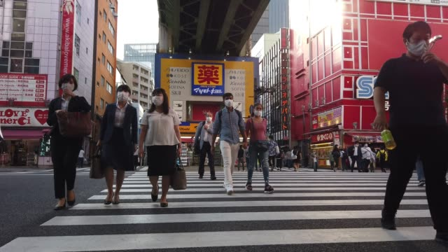 people, many wearing face masks, cross a road in the akihabara district on october 02 in tokyo, japan. the japanese government today announced that... - cross stock videos & royalty-free footage