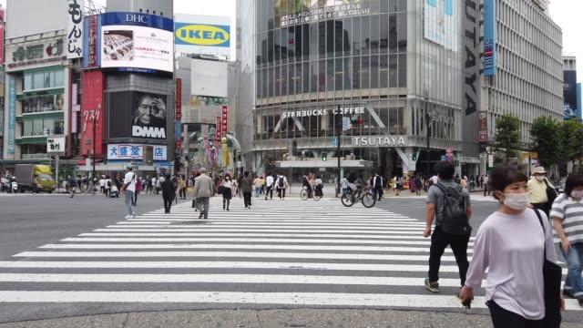 people, many wearing face masks, pass over shibuya crossing on july 29, 2020 in tokyo, japan. tokyo has reported 250 new cases of covid-19... - tokyo japan stock videos & royalty-free footage