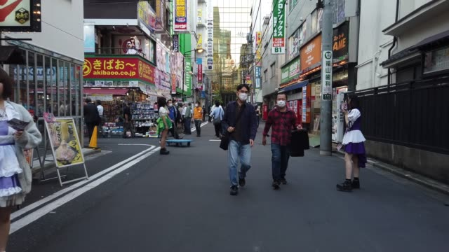 people, many wearing face masks, walk along a street in the akihabara district on october 02 in tokyo, japan. the japanese government today announced... - japan stock videos & royalty-free footage