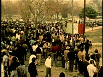 people march down street raising their fists in the air, chanting and carrying various flags and placard signs inscribed with chicano power slogans .... - 1972 stock videos & royalty-free footage