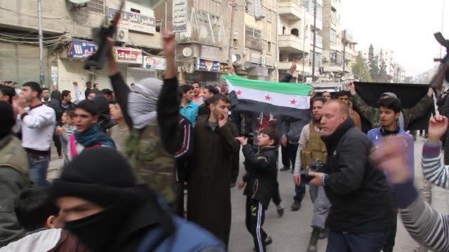 people march in the streets in protest of the syrian regime - braccio umano video stock e b–roll