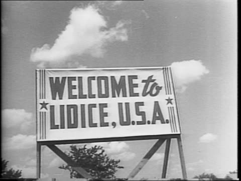people march through the village in czech republic, a cart carries a bell to church / sign outside of lidice, il / american citizens gathering in... - ゲシュタポ点の映像素材/bロール
