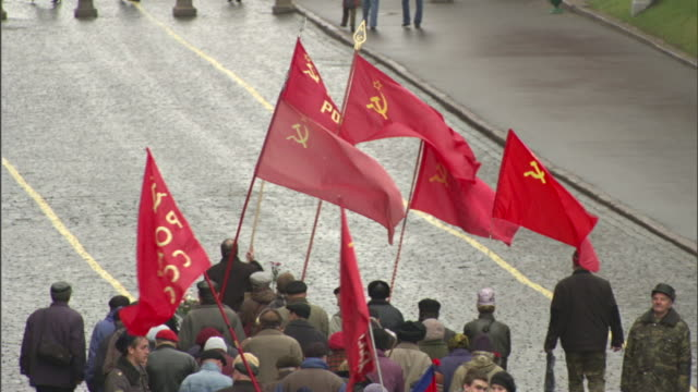 people march with flags in moscow's red square. - red square stock videos & royalty-free footage