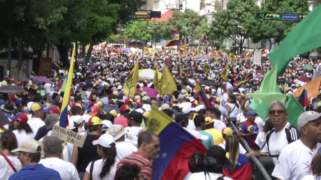 vídeos de stock, filmes e b-roll de thousands march against maduro his government in caracas 1 ws of people marching 2 cu of a guy with painted flag 3 cu of banner 4 ws of a venezuelan... - venezuela