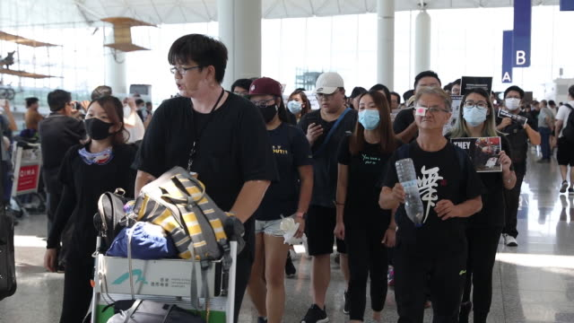 vidéos et rushes de people marching at hong kong international airport during hong kong protests, hong kong, china, on tuesday, august 13, 2019. - personne non reconnaissable