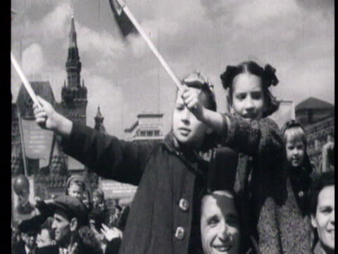 people marching with flowers, holding stalin's posters while stalin smiling and saluting from rostrum, kids cheering carrying flowers / moscow,... - 1948年点の映像素材/bロール