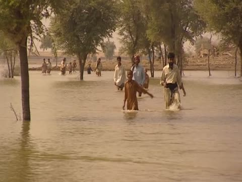people marooned on an embankment following devastating pakistan floods wade through river a boy drinks the river water - embankment stock videos and b-roll footage