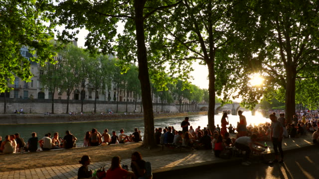 stockvideo's en b-roll-footage met people meeting on the banks of the seine river at sunset, tracking left - seine