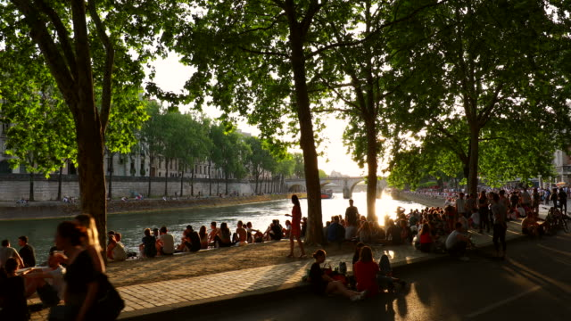 people meeting on the banks of the seine river at sunset, tracking right - river seine stock videos & royalty-free footage
