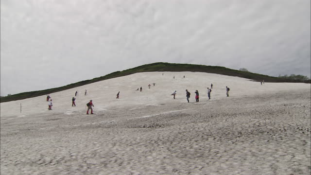 people mill about on snowy slope, zoom in as snowboarder slaloms down course, mount taisetsu, hokkaido - slalom skiing stock videos & royalty-free footage