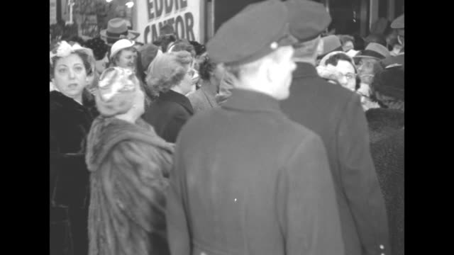 People milling about in front of the Paramount Theater prior to premiere of The Eddie Cantor Story several women in fur coats / MC Robert Alda...