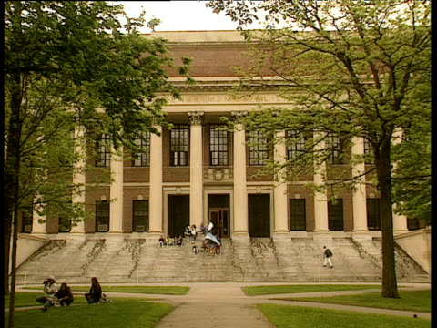 stockvideo's en b-roll-footage met people milling around exterior of harvard university. students on steps and people sitting on grass in foreground - harvard university