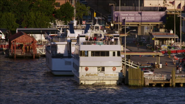 People mingle aboard yacht tied to dock on the Hudson River.