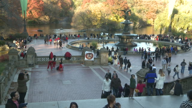 vídeos de stock e filmes b-roll de ms people mingling around bethesda fountain in autumn in central park / new york, new york, united states - fonte bethesda