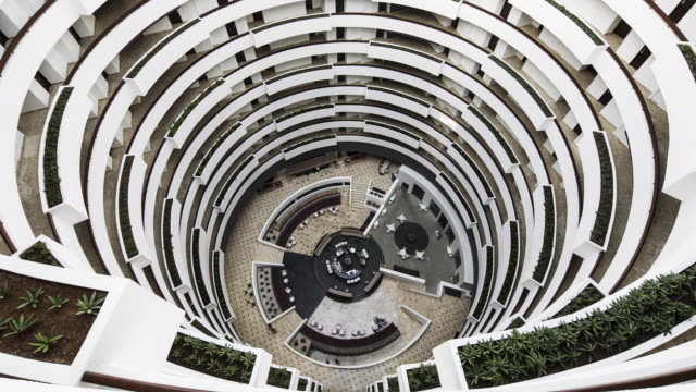 TL, WS People move around a building's central atrium / Cancun, Mexico
