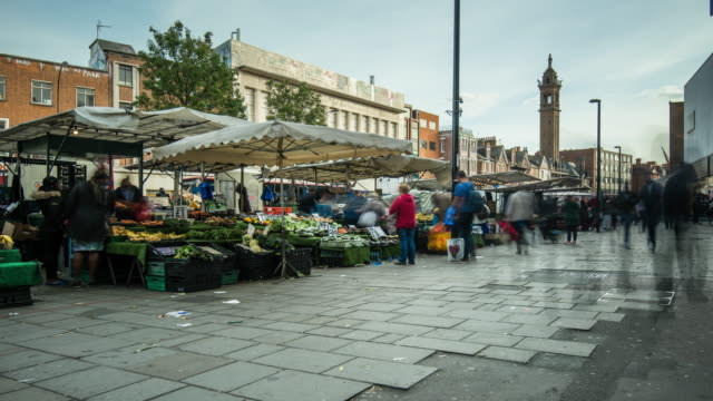 people move pass and stop to shop at a vibrant busy local fruit and vegetable street market on lewisham high street in south east london - consumerism stock videos & royalty-free footage