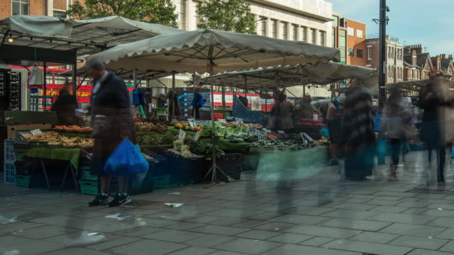 people move pass and stop to shop at a vibrant busy local fruit and vegetable street market on lewisham high street in south east london - stereotypically working class stock videos & royalty-free footage
