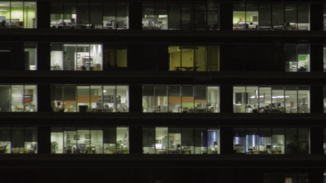 t/l ms zo people moving around and lights turning on and off inside office building at night/ sydney, australia - office block exterior stock videos & royalty-free footage