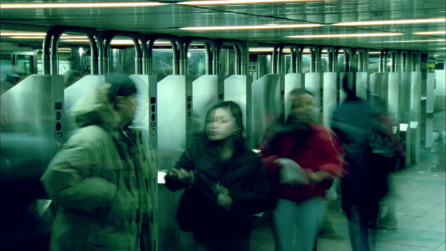 TL MS People moving in and out of subway station turnstiles/ New York City