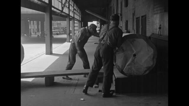 qs people moving in the dark / mls men unloading rolls of paper from truck roll them up ramp to chute platform trap door device drops rolls into... - 自動車ブランド mini点の映像素材/bロール