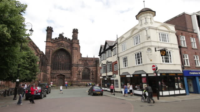 ws people moving on intersection infront of ornate church / chester, england - 英国チェスター点の映像素材/bロール