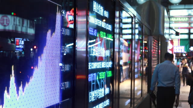 people moving past screen showing stock chart at night - 国際金融点の映像素材/bロール