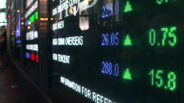 people moving past screen showing stock market data at night - 国際金融点の映像素材/bロール
