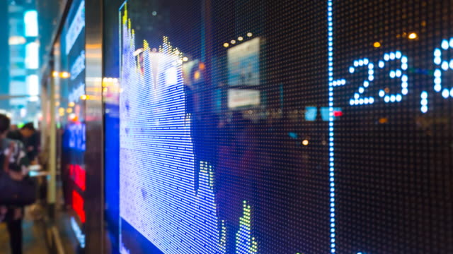 People moving past stock market quote display screen
