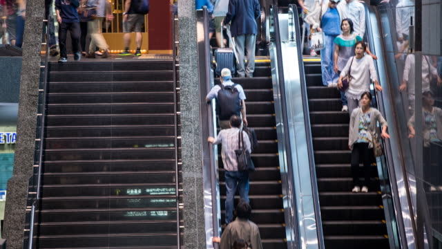 People moving up and down escalators and stairs