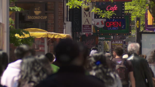 people navigate a busy sidewalk in the restaurant district on king street in toronto canada.  the sidewalk is filled with people walking by. - toronto stock videos & royalty-free footage
