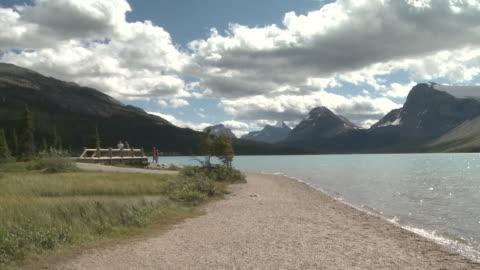 ws people near shore of lake / banff national park, alberta, canada - banff nationalpark stock-videos und b-roll-filmmaterial