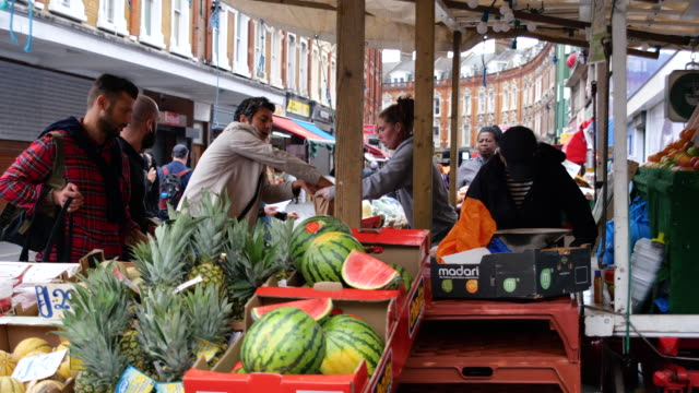 people obey social distance rules and do not wear face masks whilst shopping at electric avenue brixton marketduring lockdown for coronavirus... - high street stock videos & royalty-free footage