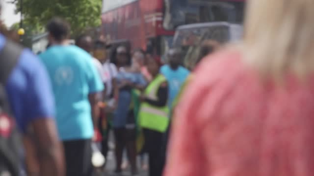 People observe a minute's silence to remember the victims of the Grenfell Tower at the Notting Hill Carnival in West London