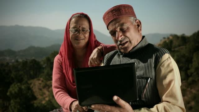 persone di himachal pradesh: coppia senior utilizzando il computer portatile - cultura indiana video stock e b–roll