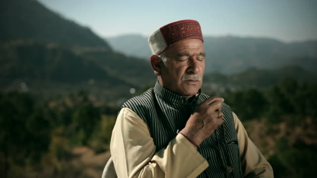 People of Himachal Pradesh: Senior man meditating with beads chant