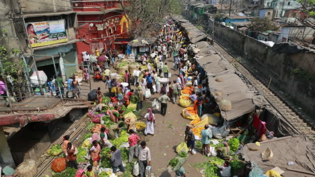 people on a market in kolkata (city of joy) next to a rail from above - kolkata stock videos & royalty-free footage
