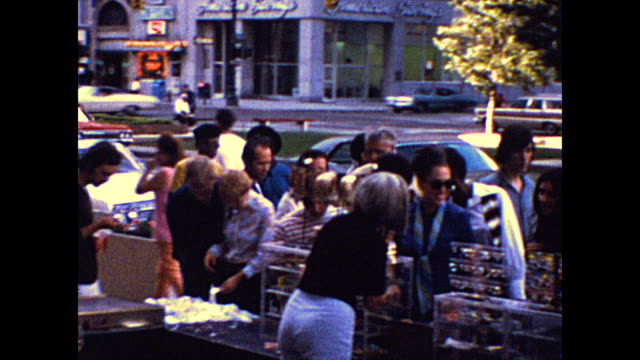 people on a new york city sidewalk look at goods laid out on tables. - flea market stock videos & royalty-free footage