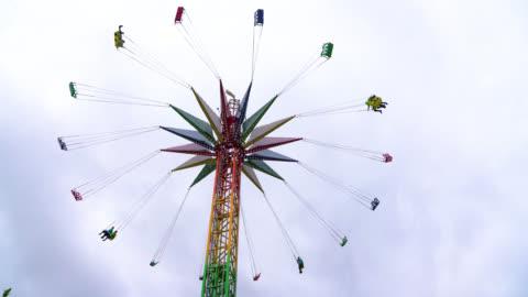 vídeos de stock e filmes b-roll de people on a swing ride at the amusement park having fun - circle