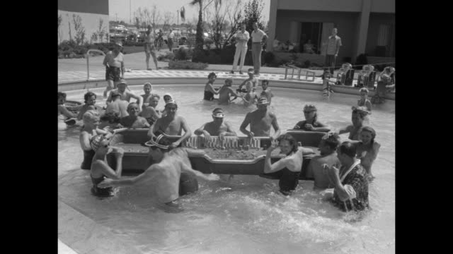 people on and standing by lawn chairs poolside at sands hotel in 1950s las vegas nevada / ms middleaged man in robe standing at edge of pool tries to... - bathrobe stock videos & royalty-free footage
