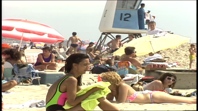 people on beach in neon colored bathing suits in oceanside california - oceanside stock videos and b-roll footage