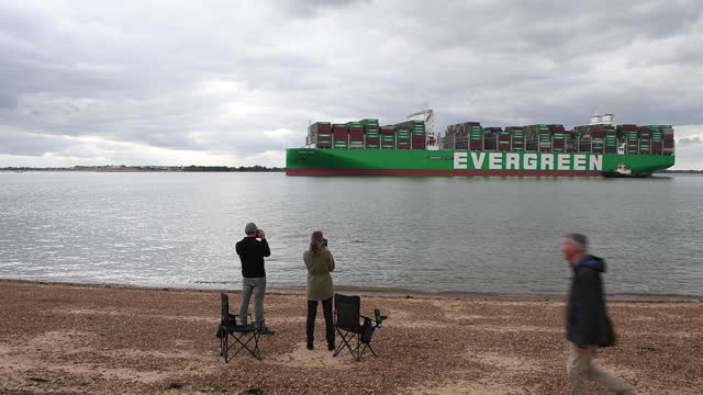 people on beach photographing world's largest container ship, ever ace leaving port of felixtowe, in felixstowe, suffolk, england, u.k., on... - western script stock videos & royalty-free footage