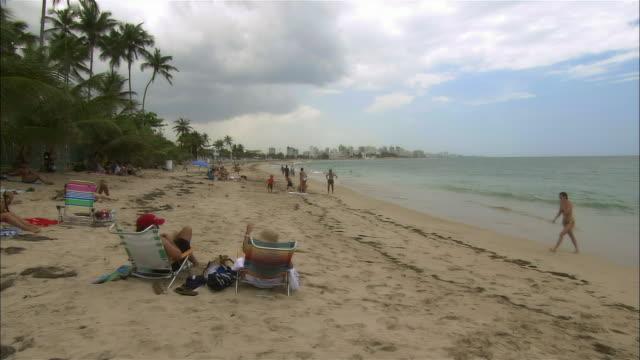 stockvideo's en b-roll-footage met ms, pan, people on beach, san juan, puerto rico - waaierpalm