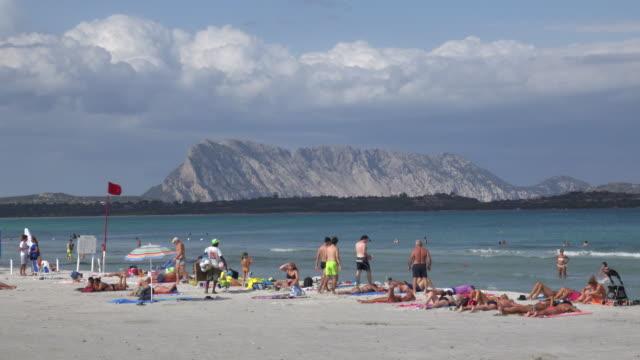 people on beach with isola tavolara - sassari stock videos & royalty-free footage