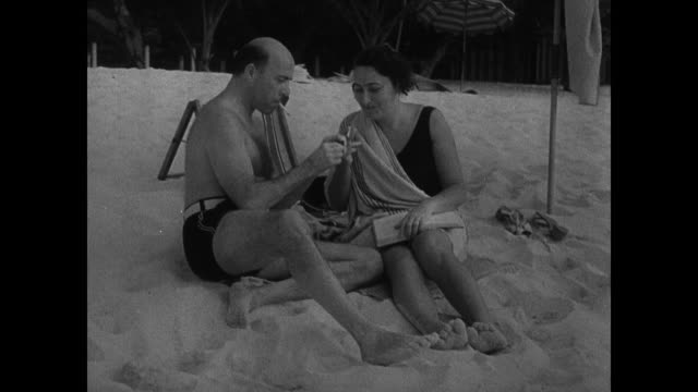 people on beaches sitting in sun relaxing woman tossing sand on man young adult male smoking cigarette people sitting on beach benches watching ocean... - 1937 stock videos and b-roll footage