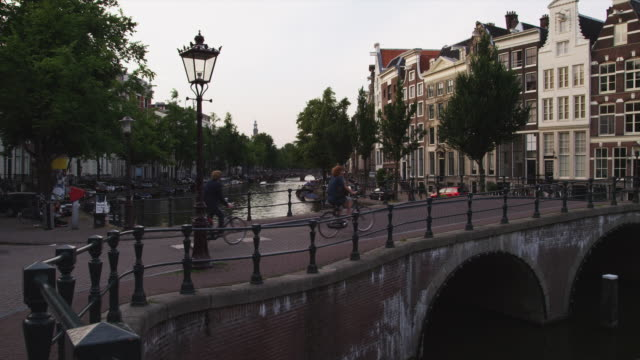 ws pan people on bicycles crossing bridge on canal / amsterdam, netherlands - canal stock videos & royalty-free footage