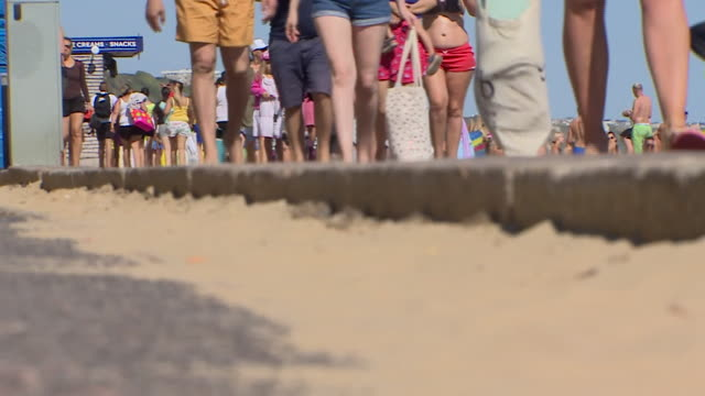people on bournemouth beach during the coronavirus lockdown - bournemouth stock-videos und b-roll-filmmaterial